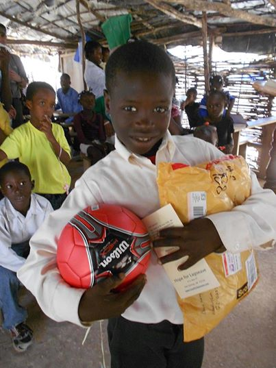 A happy student with a package from his sponsor family